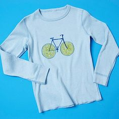 A lemon slice makes a perfect bike wheel!                 Cut a lemon in half and let it dry overnight. Dab paint on it with a brush and stamp 2 circles on your t-shirt about an inch apart. Let dry, then use a fabric marker to draw the bike frame, pedals, seat and handlebars.