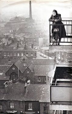 """I love this photo, which is mentioned in the Morrissey autobiography. He says his friend lived in the block of modern flats she is in, """"at the junction of Cornbrook street and Chorlton Road, where Moss Side creeps up on Old Trafford."""" Photo is of the character Ena Sharples from Coronation Street, which I've never seen. But it shows the sort of old 19th century dwellings and a factory, and she is in a post-'slum clearance' new building. From http://coronationstreetupdates.blogspot.co.uk/"""