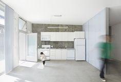 love the white cabinetry over rough concrete.
