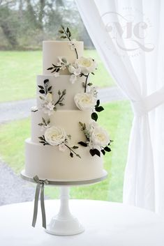 White wedding cake with trailing white flowers and greenery by Mama Cakes Cumbria