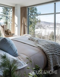 Warm beige and grey fabrics balance out the cool scenery beyond the large windows of the principal bedrooms. | Photographer: André Rider | Designer: Richard Ouellette, Les Ensembliers