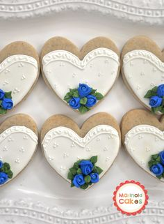 "Bride and Groom Cookies, Royal Blue Rosebud Bouquet - These  cookies flew to Guam this June. I am happy to announce, not one cookie broke. All 105 of them arrived safe! Thanks USPS. And my friend's first words were... ""They are sooo beautiful and they really smell so good!"" :-)    3.5  x 3.5 heart cookies covered in royal icing and fondant. Cookies were vanilla spiced orange sugar cookies."