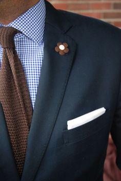 ネイビースーツにギンガムチェックのシャツ、ブラウンのニットタイ、白チーフを合わせて着こなす