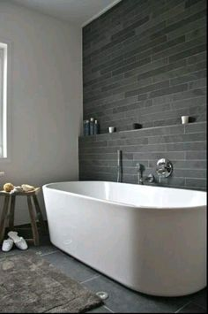 modern bathroom with soaking tub + grey tile + tiled shelf