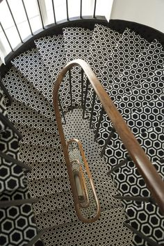 Great black + white tiles contrasting with the brass bannister.