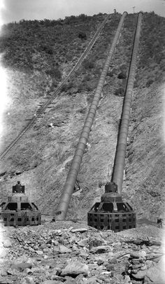 Two men are digging through the rubble around the generators that were left behind after the St. Francis Dam failed on March 12-13, 1928.  The generators, which produce electricity along L.A.'s gravity-fed water delivery system, are supposed to have a big building around them (this one), but it has washed away.