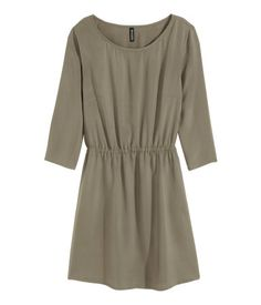 Short dress in woven fabric. 3/4-length sleeves, elasticized seam at waist, and side pockets. Unlined.