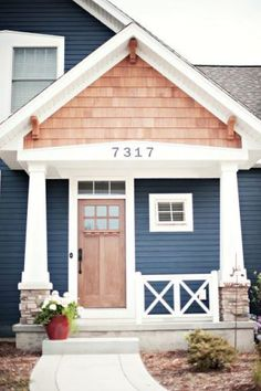 Navy house, white trim, wood door