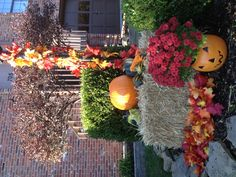Fall Outside Decor-  Hay barrel, Pumpkin, Gourds, Mum places in plastic pumpkin Fake leaves sticking out of hay and wrapped around light post.