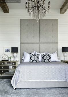 Chic gray bedroom with gray tufted tall headboard, Borghese mirrored chest, blue geometric bedding, European shams with gray frame, striped gray & black velvet pillows and crystal chandelier.
