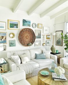 A cozy beach cottage living room with a seaside-inspired gallery wall and vaulted ceiling.