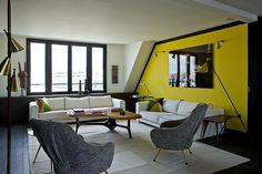 Jaune vif sur un seul mur dans le salon : en association avec le noir et le blanc, voici un constraste très élégant.