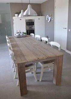 großer Esstisch in der Mitte, teilt die Küche, graue wände mit weiß kombiniert