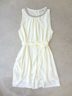 """Enchanting ivory dress finished with a sparkling neckline. Slip on dress, keyhole back and fully lined. Finished with a coordinating sash for a feminine silhouette. Polyester. Imported. Length: 35"""""""