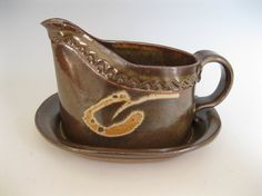Gravy boat with attached tray by TheBrickyard on EtsyThis slab-made stoneware pitcher is just the right size for gravy or a sauce you've whipped up. Made from a flat slab, it is first impressed with a little design around the upper edge, then it's formed into a pitcher shape. The tray on the bottom is firmly attached to catch the spills or drips.