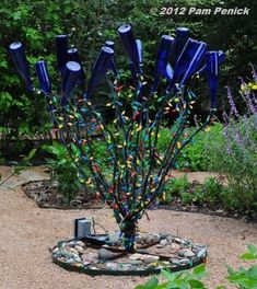 It used to be that you could see bottle trees scattered all over the Southern landscape. Usually in the country or along the bayous of Louisiana, Mississippi, Tennesee, and Alabama, bottle trees are a colorful folk tradition with the purpose of. Glass Garden Art, Bottle Garden, Glass Art, Bottle House, Wine Bottle Trees, Wine Bottle Crafts, Wine Bottles, Garden Whimsy, Garden Junk