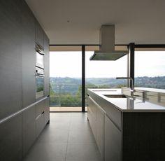 De keukenkasten bestaan uit donkere en aluminium elementen wat een moderne maar ook een soort van warme gevoel geeft. De grote ramen geven veel lichtinval en er is buiten ook heel mooi uitzicht.