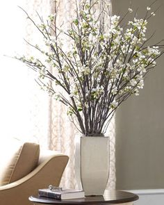Delightful faux floral arrangement comprises apple blossom sprays and birch branches in a hand-glazed, sand-colored ceramic container. Imported.