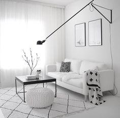 Valkoista ja valoa olohuoneessa, josta löytyy myös mustia yksityiskohtia