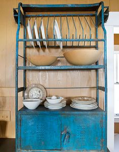 Simple storage options help a kitchen function more efficiently. A dish rack is a space-saving and attractive feature to store plates at the ready.   - CountryLiving.com