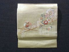 This is an elegant Nagoya obi with a design of 'housouge'(large karabana flower) and seasonal flowers on circle, which is woven