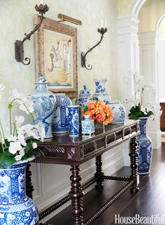 Entrance hall, love this dark wood British table covered in Blue and White porcelain. One pop of orange!