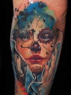An incredible tattoo by Alex de Pase of a pretty girl wearing sugar skull face paint for the Day of the Dead.