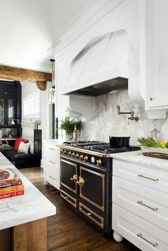 Spectacular kitchen with white shaker cabinets paired calcutta marble countertops and calcutta marble slab backsplash. White wood paneled kitchen hood over La Cornue CornuFe Stove with swing-arm pot filler over rustic wood floors.