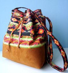 Bolsa Saquinho em tecido 100% algodão dublado, com estampa folk. Fundo em camurça caramelo.  Bolso frontal com zíper. Forrada e com bolso interno. Alça regulável  Medidas: altura: 32 cm largura: 26 cm profundidade: 15 cm R$ 88,00
