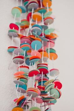 Simple divine. DIY Confetti Garland by subtlerevelry: Made with a Martha Stewart Circle Paper Punch, 12 sheets of multi colored card stock, a silver cord, by belphegor