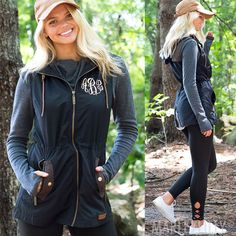 Layer our cute hooded utility vest over any sweater or tunic! This black and brown vest is made of polyester and has a cinch waist for a flattering fit. The cording matches our Monogrammed Duck Boots perfectly.