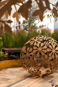 metal wall sculptures by Entanglements. 'Flower Ball' metal artwork in a wrought iron-like finish into your outdoor living space. Easy backyard art ideas to incorporate into your yard area.