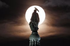 The supermoon, behind the bronze Statue of Freedom, atop the U.S. Capitol, on 8/10/14, in Washington, D.C. (AP Photo/Alex Brandon)