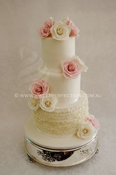 Ivory wedding cake with ivory and pink sugar roses, and tier of fondant ruffles. Gorgeous! By Sweet Perfection.
