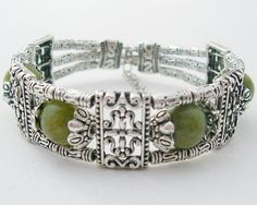This is a gorgeous Tibet Silver Brass Green Jade beaded Bracelet with adjustable clasp. This bracelet has very exotic and modern design. Has 4 beautiful green jade beads.  The bracelet is 2cm wide. The beads measure 1x1cm each.