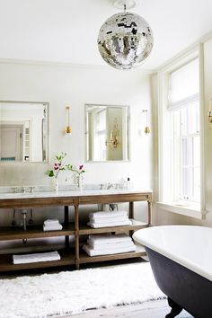Disco ball hanging in beautiful white bathroom with black tub