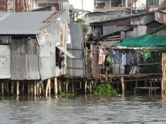 River-side houses on the Mekong River, Vietnam near the floating market. These houses on stilts offer a unique view into the everyday life of the local Vietnamese community and how they live.