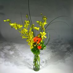 Yellow dendrobium orchids and orange spray roses