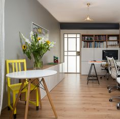 A small office. A yellow chair behind a white table. By Liat Hadas, Architecture & Design.