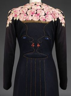 The back bodice designed by Jean Cocteau and embroidered by Maison Lesage with confronting facial profiles in gold thread forming a shaped vase filled with roses of tucked pink silk and leaves of green thread decorating the upper back and shoulders, the eyes of a blue stone and the lips of red foil, the centre back skirt with applied gold thread to imitate pleats.