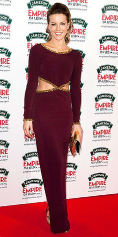 Who: Kate Beckinsale Dress: The British actress rocked a burgundy Jenny Packham fall 2014 long sleeve rib cage cut-out gown with spiked gold trimmings. She accessorize with a gold envelope clutch and...