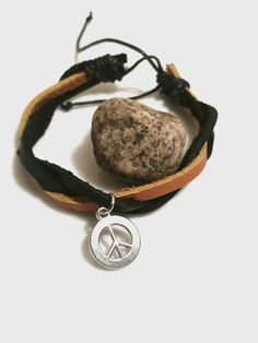 "Nice silver peace sign charm on genuine leather. Charm is approximately 1/2"" Bracelet is adjustable."