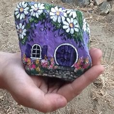 Painted on hard stone, this little purple decorative garden house can withstand the outdoors or live comfortably in a potted plant. A daisy roof and round door adds whimsy to your garden decor and suggests that little gnomes or fairies may have taken residence in among your plants.  The purple daisy house measures almost 3 tall, almost 3 1/2 wide, and about 2 1/4 deep.