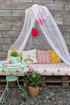 Un rincón en la  terraza con palets en tonos pastel