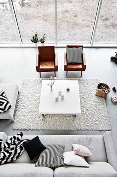 deco scandinave salon, panier en fibres végétales, canapé en gris avec coussins décoratifs, fauteuil en cuir marron