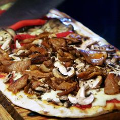 The ultra-thin, delicate dough is grilled over hot coals on one side for five minutes, then flipped over and topped with minimal ladles of red sauce, a variety of fresh ingredients, and cheese, before being grilled for five to seven minutes longer. The result: a cracker-thin crust that crunches with every bite, joining two culinary rites of passage.