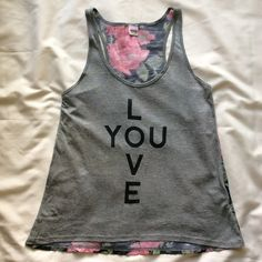 """""""Love You"""" Tank Top with Floral Back Only worn a couple times and is in perfect condition. Fits more like a small (extra small if you have a B+ chest size). Material: Self: 100% rayon; Contrast: 100% polyester. Measurements: Chest: 16 inches; Length: 23 inches. (CURRENTLY NOT TRADING) Tops Tank Tops"""