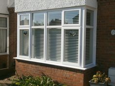 Exterior view of box bay window. Plantation shutters in white finish it a treat.