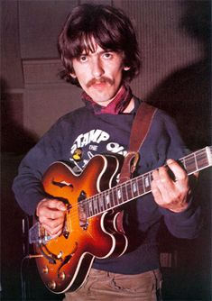 """George Harrison wearing his """"Stamp Out The Beatles"""" sweater during a recording session for Sgt. Pepper's Lonely Hearts Club Band in early 1967"""