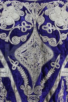Detail of an elaborately embroidered purple velvet waistcoat, Balkan, late 19th century, adorned with broad bands of woven silver braid and couched silver threads.